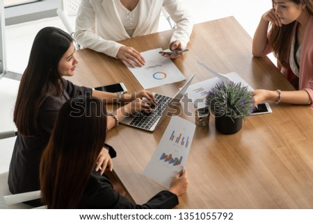Businesswoman in group meeting discussion with other businesswomen colleagues in modern workplace office with laptop computer and documents on table. People corporate business working team concept. #1351055792