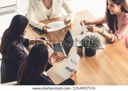 Businesswoman in group meeting discussion with other businesswomen colleagues in modern workplace office with laptop computer and documents on table. People corporate business working team concept. #1354907555