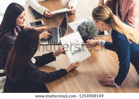 Businesswoman in group meeting discussion with other businesswomen colleagues in modern workplace office with laptop computer and documents on table. People corporate business working team concept. #1354908149