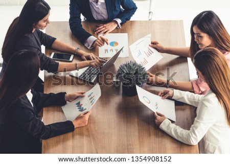 Businesswoman in group meeting discussion with other businesswomen colleagues in modern workplace office with laptop computer and documents on table. People corporate business working team concept. #1354908152
