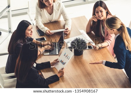 Businesswoman in group meeting discussion with other businesswomen colleagues in modern workplace office with laptop computer and documents on table. People corporate business working team concept. #1354908167