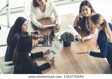 Businesswoman in group meeting discussion with other businesswomen colleagues in modern workplace office with laptop computer and documents on table. People corporate business working team concept. #1363770644