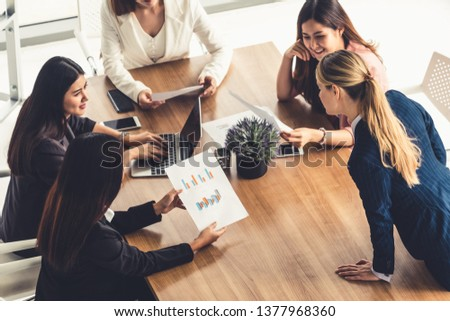 Businesswoman in group meeting discussion with other businesswomen colleagues in modern workplace office with laptop computer and documents on table. People corporate business working team concept. #1377968360