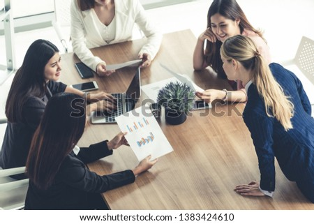 Businesswoman in group meeting discussion with other businesswomen colleagues in modern workplace office with laptop computer and documents on table. People corporate business working team concept. #1383424610