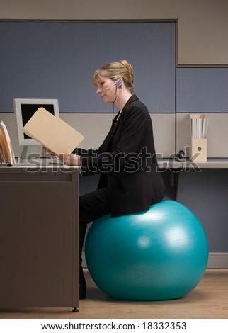 Businesswoman in headset looking at file folder while sitting on exercise ball at desk in cubicle - stock photo