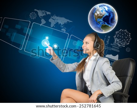 Businesswoman in headset sitting on chair, using touch screen interfaces. Globe above, with blue technology background. Element of this image furnished by NASA