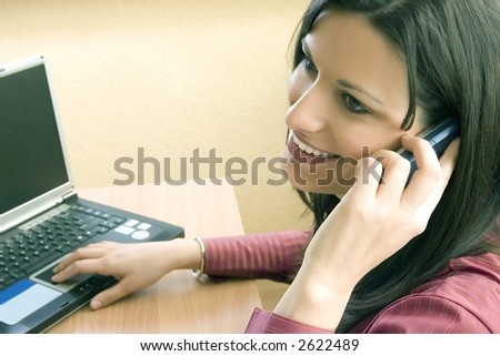 Businesswoman in her office talking on phone - stock photo
