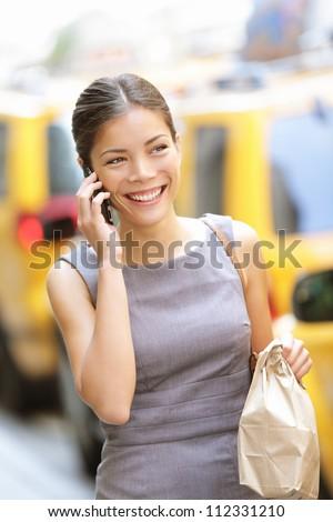 Businesswoman in New York talking on the phone walking busy with lunch break doggie bag smiling happy. Young beautiful multiracial Caucasian / Chinese Asian business woman.