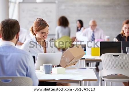 Businesswoman In Office Booking Courier Collection