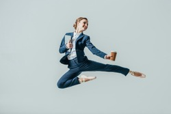 businesswoman in suit and ballet shoes jumping with coffee and digital tablet, isolated on grey
