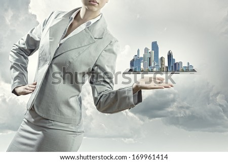 Businesswoman in suit holding tablet pc on palm #169961414