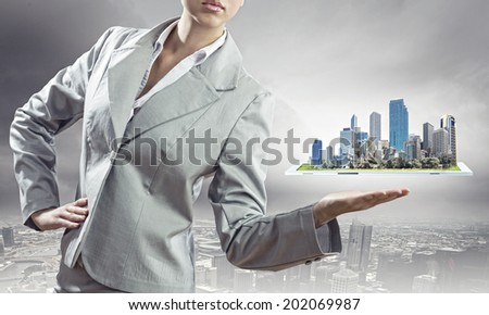 Businesswoman in suit holding tablet pc on palm #202069987