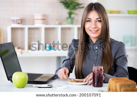 Businesswoman in the kitchen preparing breakfast. She is smearing jam on bread before going to work.