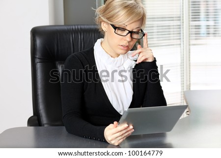 businesswoman in the office at the table working on the touch pad tablet phone gadget.