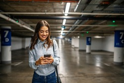 Businesswoman in underground garage. Elegant woman using smartphone in parking garage. Fashionable young woman texting on smartphone. Businesswoman in a parking garage