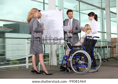 Businesswoman in wheelchair with colleagues