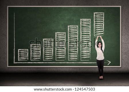 Businesswoman inside a diagram is pushing the bar upward