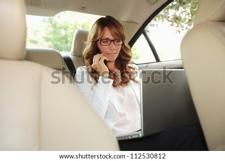 Businesswoman inside her car using a laptop and a mobile phone