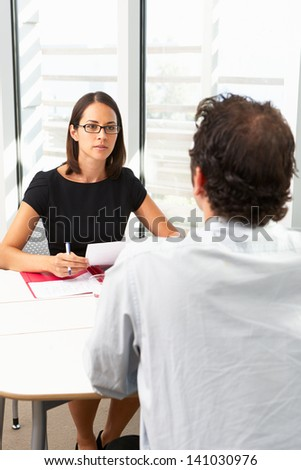 Businesswoman Interviewing Male Candidate For Job - stock photo