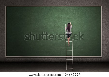 Businesswoman is climbing a ladder in front of a blackboard