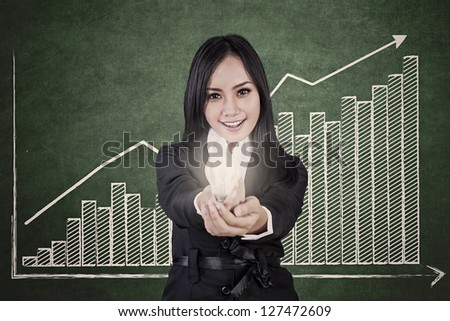 Businesswoman is holding a bright light bulb with profit bar chart showing increase in value - stock photo