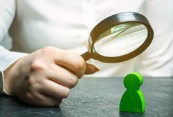 Businesswoman is holding a magnifying glass over a green man figure. Search for a talented employee. Identifying strengths in the company. Disclosure skills. Employee characteristics