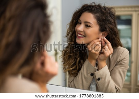Businesswoman is  putting earrings while preparing for work. Foto stock ©