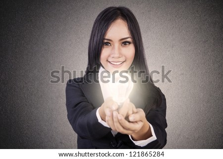 Businesswoman is smiling while giving a lit light bulb