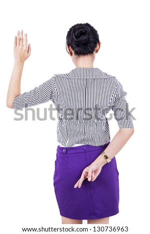 Businesswoman is standing with her fingers crossed behind her back