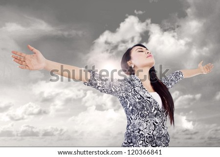 Businesswoman is stretching her arms expressing her winning outdoor