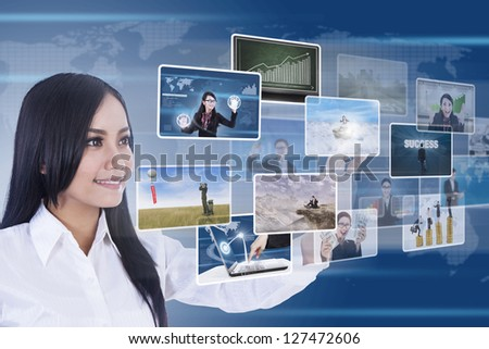 Businesswoman is using digital touchscreen to choose photos pictures