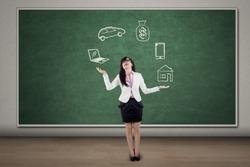 Businesswoman juggling responsibilities over blackboard in the classroom