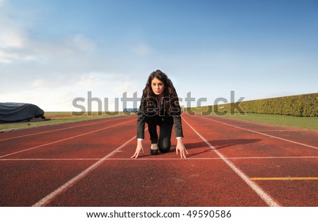 Businesswoman kneeling on the starting grid of a running track