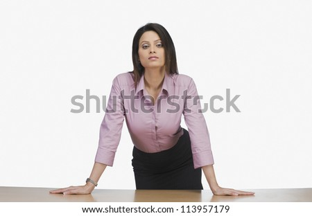Businesswoman leaning against a desk