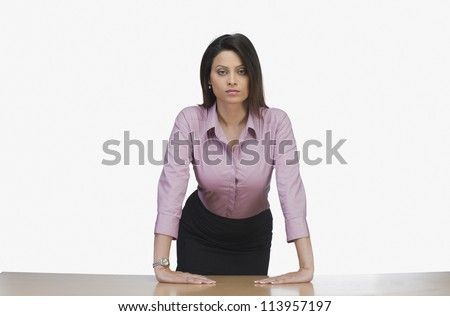 Businesswoman leaning against a desk