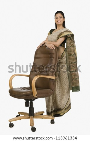 Businesswoman leaning against an office chair