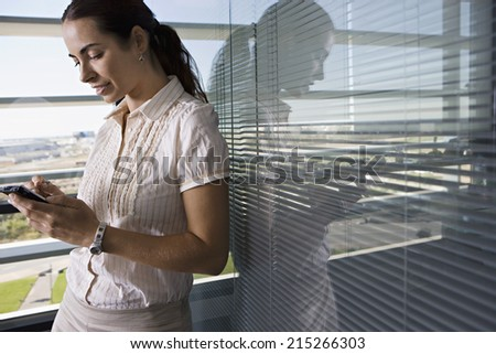Businesswoman leaning against office window, using personal electronic organiser, side view