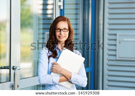 Businesswoman leaning on the door and holding a laptop