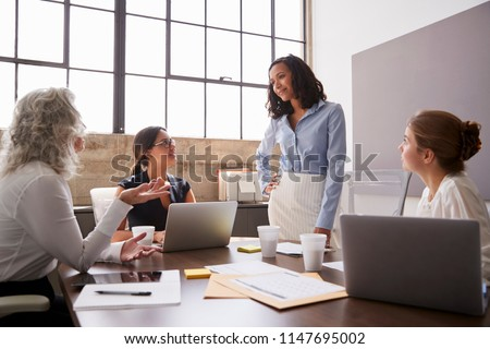 Businesswoman listening to female colleagues in a meeting