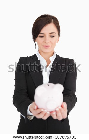 Businesswoman looking at a piggy-bank against white background