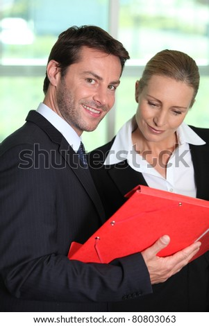 Businesswoman looking at businessman's notes