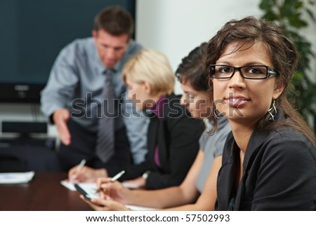 Businesswoman looking at camera during business training, smiling.