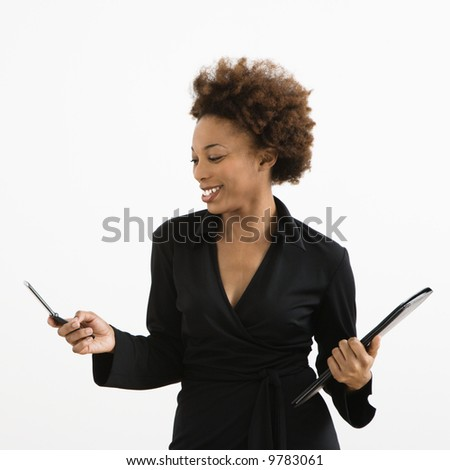 Businesswoman looking at cellphone smiling against white background.