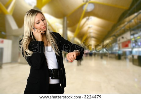 Businesswoman looking at her watch while being on the phone, standing in the departure hall of an airport, waiting to catch her flight for her business travel.