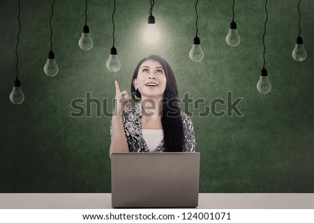 Businesswoman looking at lit light bulb in front of laptop