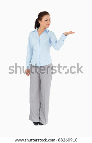 Businesswoman looking at what she is presenting against a white background