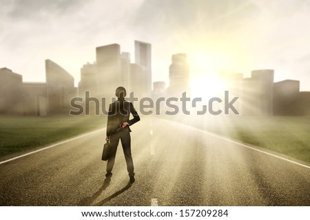 Businesswoman looking for a future and standing on the highway of a skyscraper with cityscape