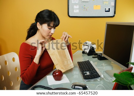 Businesswoman looking in lunch bag