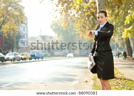 businesswoman looking in watch,  late for work or a meeting