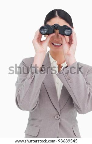 Businesswoman looking through binoculars against a white background